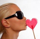 Portrait der reizvollen blonden Frau, die ihre Süßigkeit saugt Stockfoto