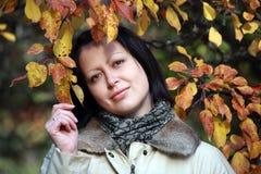 Portrait der schönen Frau in den Herbstblättern Stockfotografie