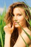 Portrait der schönen Frau im grünen Gras lizenzfreie stockbilder