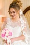 Portrait der schönen jungen Braut Ein Mädchen wirft in einem Hotelzimmer auf Eine Dame sitzt mit einem Blumenstrauß von Rosen dur Lizenzfreie Stockbilder
