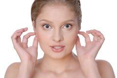Portrait der schönen jungen Frau, die ihre Ohren anhält Lizenzfreie Stockfotografie