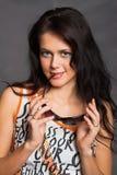 Portrait der schönen jungen reizvollen Frau auf grauem Hintergrund Stockbilder