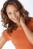 Portrait der schönen lächelnden Frau in der Orange Stockfotos