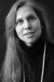 Portrait der schönen lächelnden langhaarigen Frau innen Stockbilder