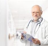 Portrait des älteren Doktors auf Krankenhausflur Stockbilder
