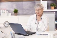 Portrait des älteren Doktors im Büro lizenzfreies stockbild