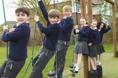 Portrait des élèves d'école primaire sur l'équipement s'élevant Photos libres de droits