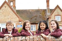 Portrait des élèves dans l'uniforme en dehors du bâtiment scolaire photos stock