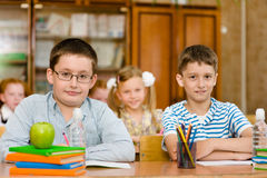 Portrait des élèves regardant l'appareil-photo dans la salle de classe Image stock