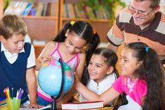 Portrait des élèves regardant le globe avec leur professeur Photographie stock libre de droits