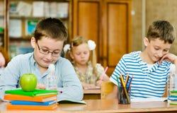 Portrait des étudiants écrivant l'examen dans la classe Photo stock