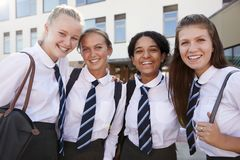 Portrait des étudiants féminins de sourire de lycée portant l'uniforme à l'extérieur du bâtiment d'université photographie stock libre de droits