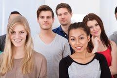 Portrait des étudiants universitaires se tenant dans la salle de classe Image stock