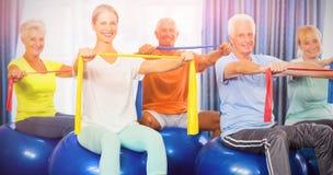 Portrait des aînés employant la boule d'exercice et étirant des bandes Images stock