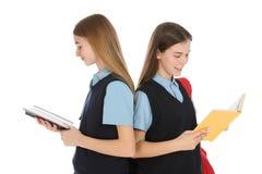 Portrait des adolescentes dans l'uniforme scolaire avec des livres sur le blanc photo stock