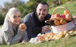 Portrait des adultes avec des pommes et des sandwitches en nature Photo stock