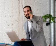 Portrait des affaires parlantes de jeune homme attirant heureux d'entrepreneur sur le mobile photographie stock