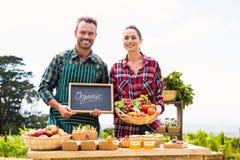 Portrait des ajouter au tableau noir et du panier vendant des légumes Image stock