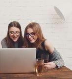 Portrait des amies riantes avec l'ordinateur portable Images libres de droits