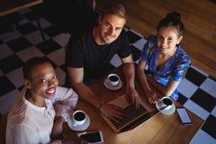 Portrait des amis à l'aide de l'ordinateur portable tout en ayant le café Photographie stock libre de droits