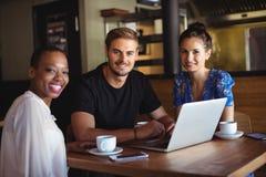 Portrait des amis à l'aide de l'ordinateur portable tout en ayant le café Images stock