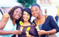 Portrait des amis africains heureux avec la crème glacée  Photo stock