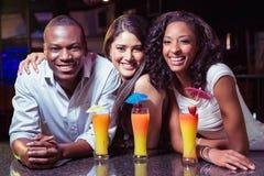 Portrait des amis appréciant tout en ayant le cocktail boit au compteur de barre Photo stock