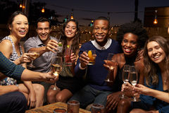 Portrait des amis appréciant la nuit à la barre de dessus de toit Photographie stock libre de droits