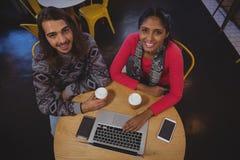 Portrait des amis avec l'ordinateur portable en café Image libre de droits