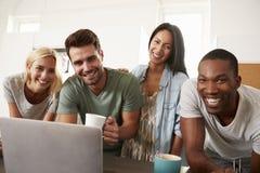 Portrait des amis avec l'ordinateur portable et le café potable dans la cuisine Images stock