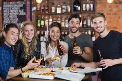 Portrait des amis ayant la pizza avec de la bière Image libre de droits
