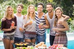 Portrait des amis ayant le jus à la partie de barbecue d'extérieur Image stock