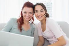 Portrait des amis décontractés à l'aide de l'ordinateur portable à la maison Image libre de droits