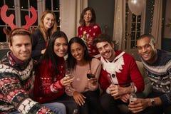 Portrait des amis dans les pullovers de fête à la fête de Noël Photographie stock