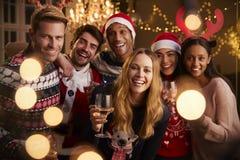 Portrait des amis dans les pullovers de fête à la fête de Noël