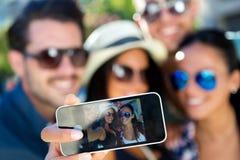 Portrait des amis de groupe prenant des photos avec un smartphone Images stock