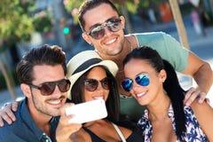 Portrait des amis de groupe prenant des photos avec un smartphone Image libre de droits