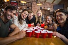 Portrait des amis de sourire autour des tasses jetables sur la table Photographie stock libre de droits