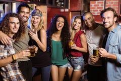Portrait des amis de sourire avec des boissons par le compteur Images libres de droits
