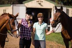 Portrait des amis de sourire avec des chevaux Photographie stock