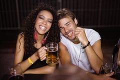 Portrait des amis de sourire avec des tasses de bière se reposant à la boîte de nuit Image stock