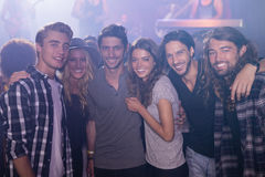 Portrait des amis de sourire avec le bras autour dans la boîte de nuit Images stock