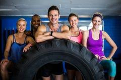 Portrait des amis de sourire avec le pneu dans le gymnase Image stock