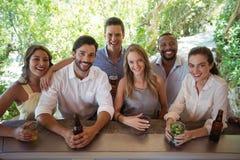 Portrait des amis de sourire ayant l'alcool au compteur Image stock