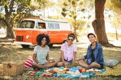 Portrait des amis de sourire ayant la nourriture tout en se reposant sur la couverture de pique-nique Photo stock