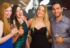 Portrait des amis de sourire buvant des bières Photographie stock libre de droits