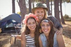 Portrait des amis de sourire contre le camping de tente à la forêt Photos stock