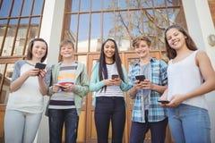 Portrait des amis de sourire d'école à l'aide du téléphone portable dans le campus Photo libre de droits