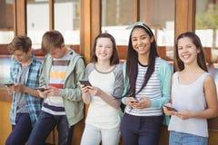 Portrait des amis de sourire d'école à l'aide du téléphone portable dans le couloir Images stock