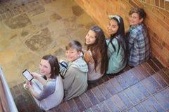 Portrait des amis de sourire d'école s'asseyant sur l'escalier utilisant le téléphone portable Photos stock